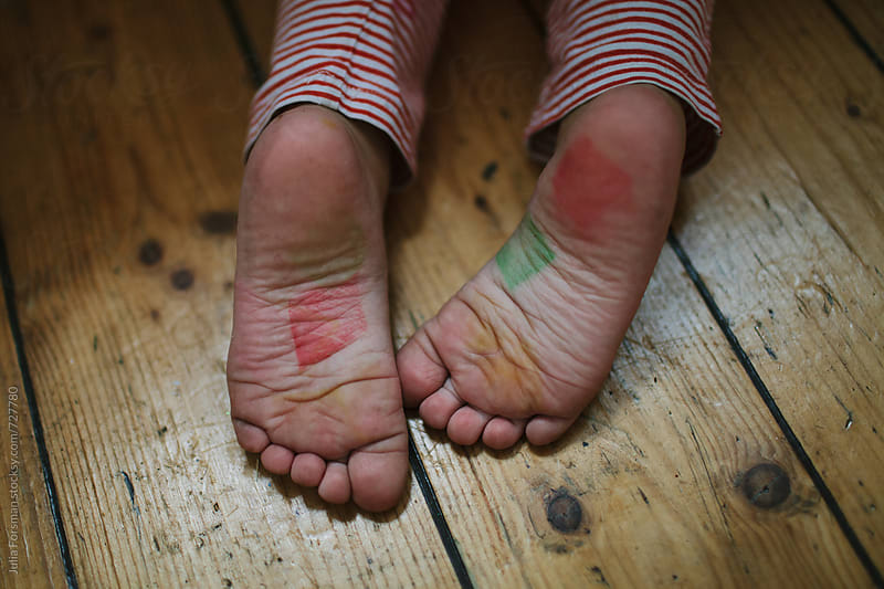 Child's feet covered in ink after a creative art session. by Julia Forsman for Stocksy United