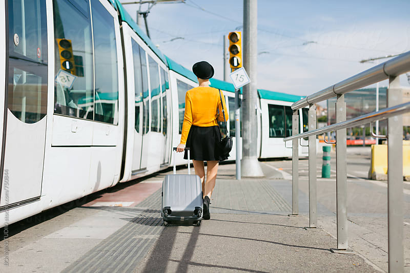 Back view of a woman walking with her suitcase on a train station. by BONNINSTUDIO for Stocksy United