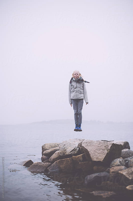 Girl hovering in the air above a pier by the sea by Jonas Räfling for Stocksy United