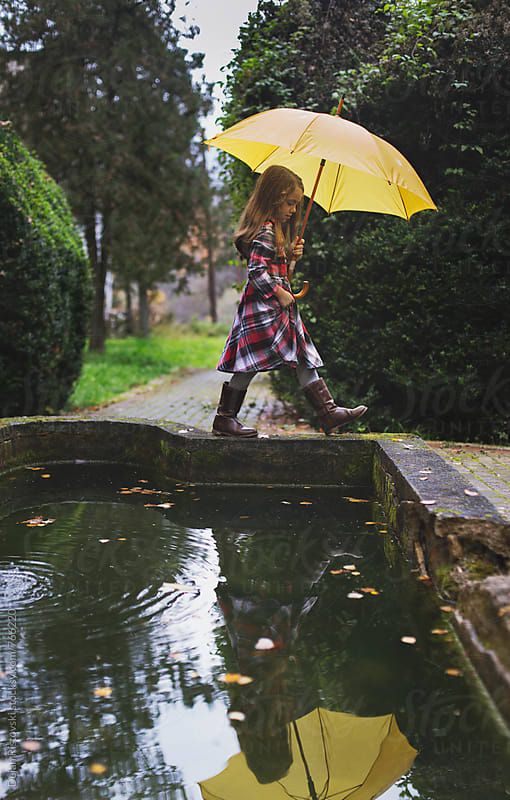 Girl with yeallow umbrella. by Dejan Ristovski for Stocksy United