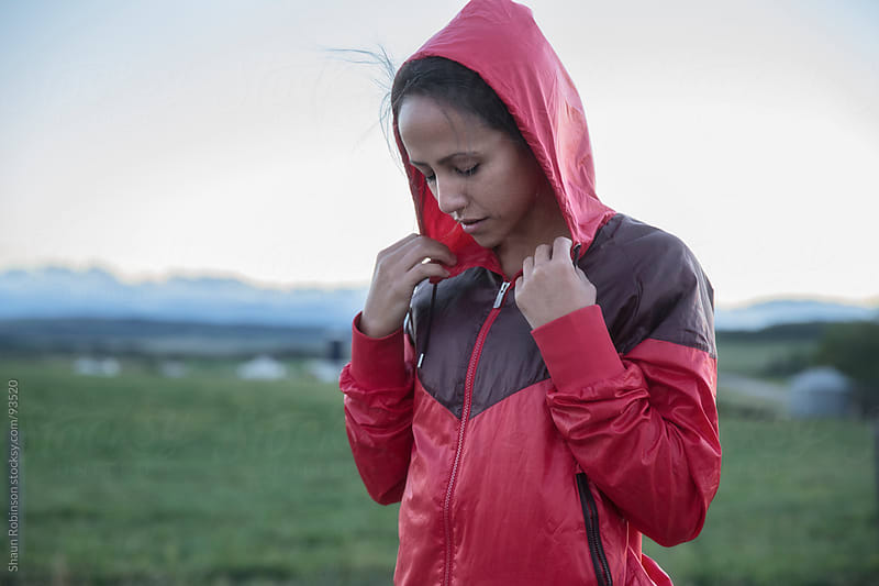 Young woman in a red windbreaker  by Shaun Robinson for Stocksy United