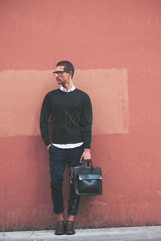 Young businessman wearing glasses and holding briefcase in front a orange wall. by BONNINSTUDIO for Stocksy United