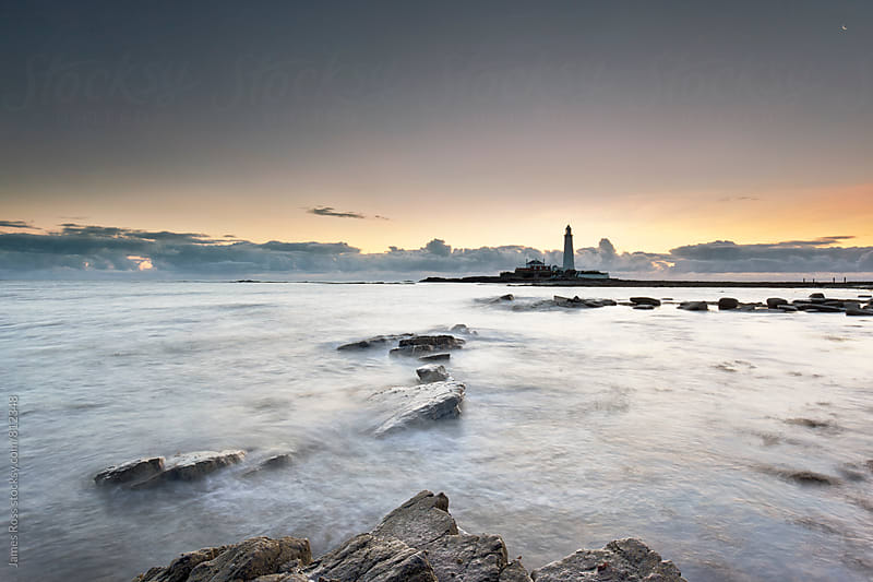 A lighthouse at dawn surrounded by water and rocks by James Ross for Stocksy United
