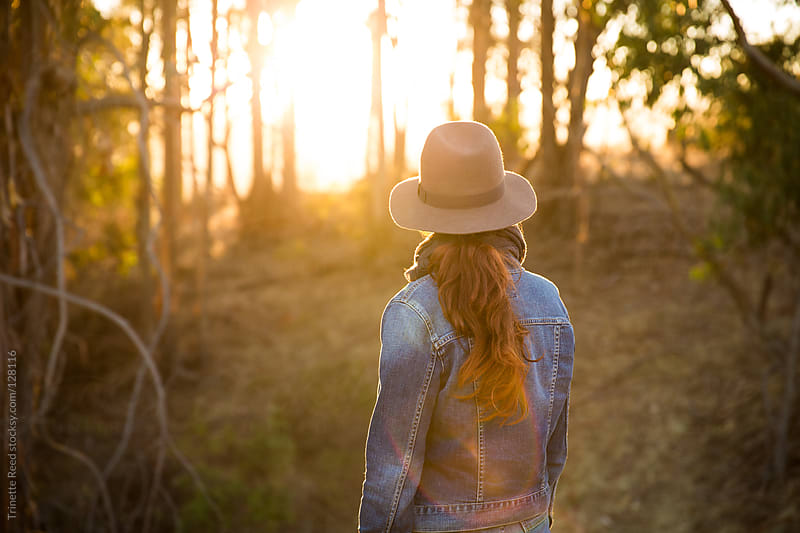 Woman standing in nature looking at sunset through the trees by Trinette Reed for Stocksy United
