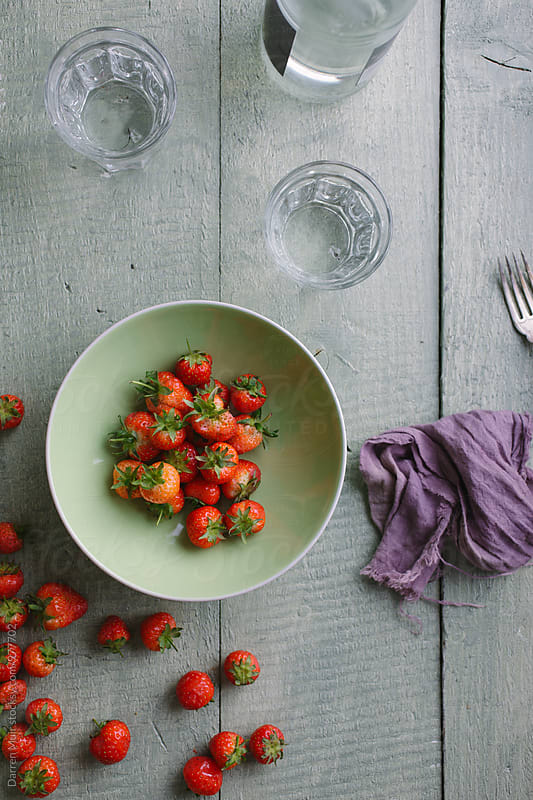 Strawberry's in a green bowl on table. by Darren Muir for Stocksy United