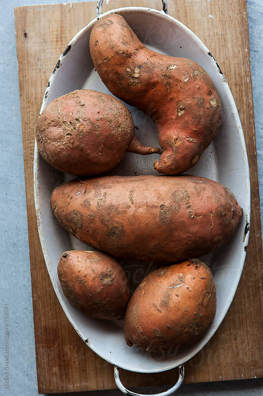 Raw sweet potatoes  by Nadine Greeff for Stocksy United