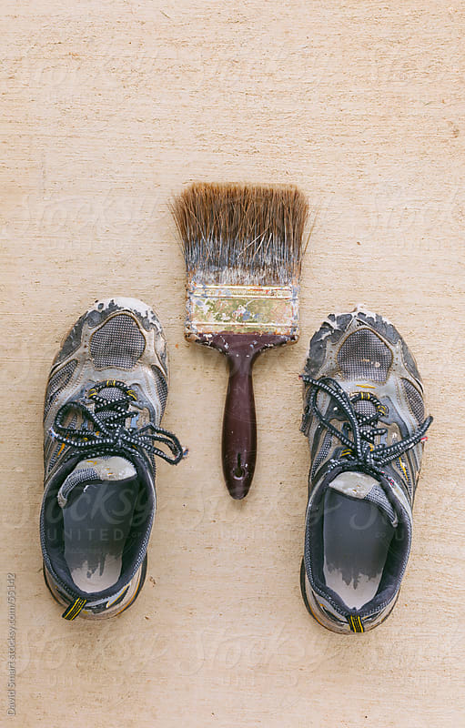 Old shoes and paintbrush on concrete surface by David Smart for Stocksy United