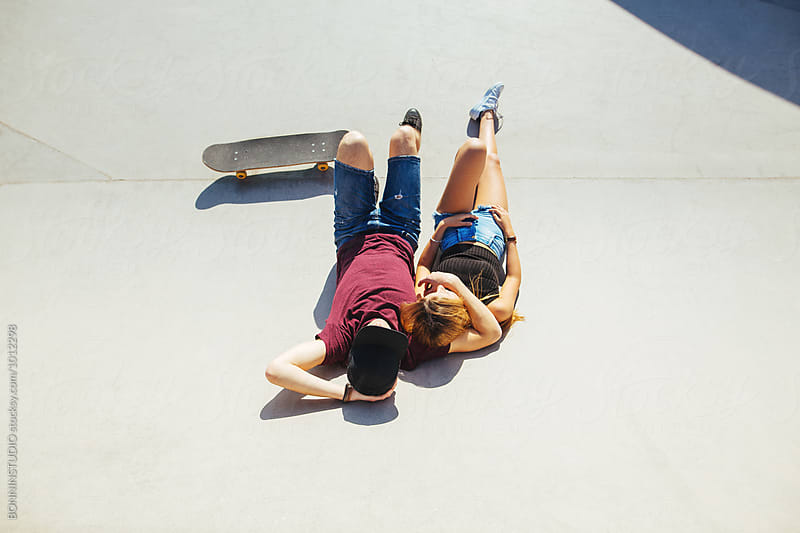 Teenage couple relaxing tanning together on a skatepark in summer.  by BONNINSTUDIO for Stocksy United