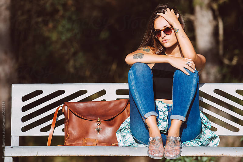 Stylish young woman sitting on a bench by Susana Ramírez for Stocksy United