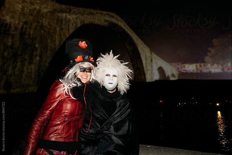 A couple in costume posing for a photo by Beatrix Boros for Stocksy United