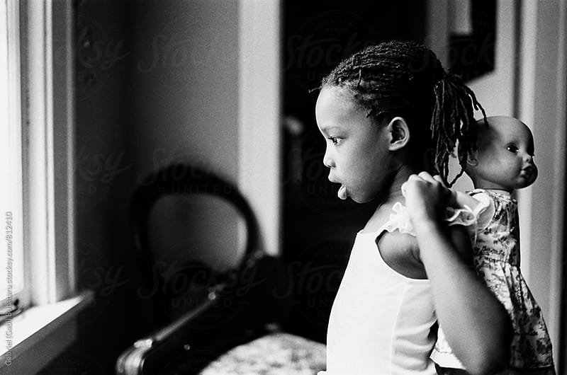 Black girl and her doll by Gabriel (Gabi) Bucataru for Stocksy United