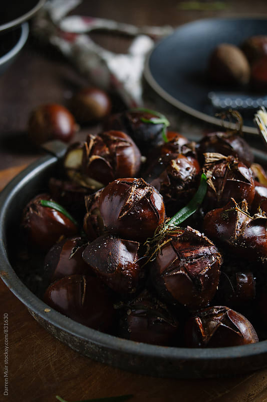 Roasted chestnuts in a metal oven tray in a rustic background. by Darren Muir for Stocksy United