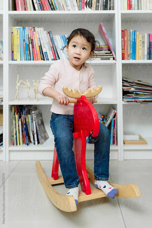 Portrait of little girl playing on rocking horse by Maa Hoo for Stocksy United