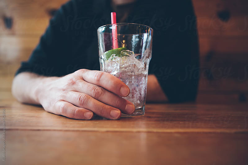 Man sitting at bar with empty cocktail, focus on hand holding  beverage by Paul Edmondson for Stocksy United