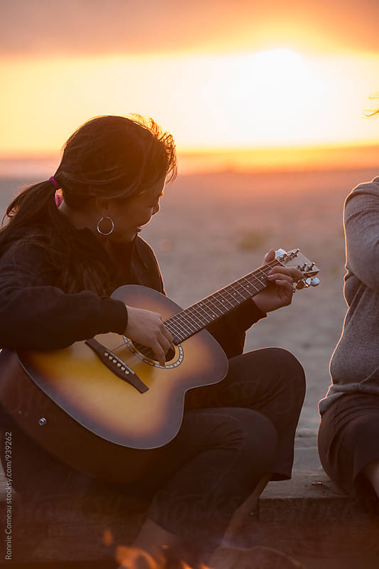 Woman Playing Guitar At The Beach At Sunset by Ronnie Comeau for Stocksy United
