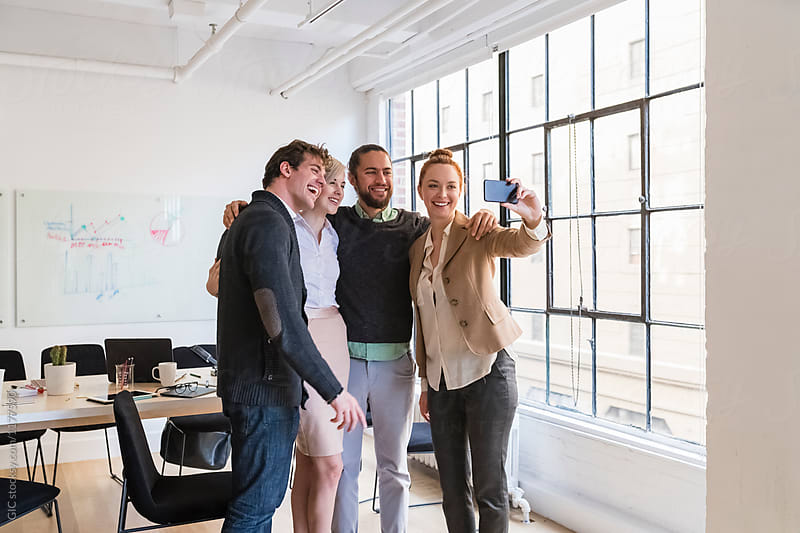 Teamwork taking a selfie together in the office
