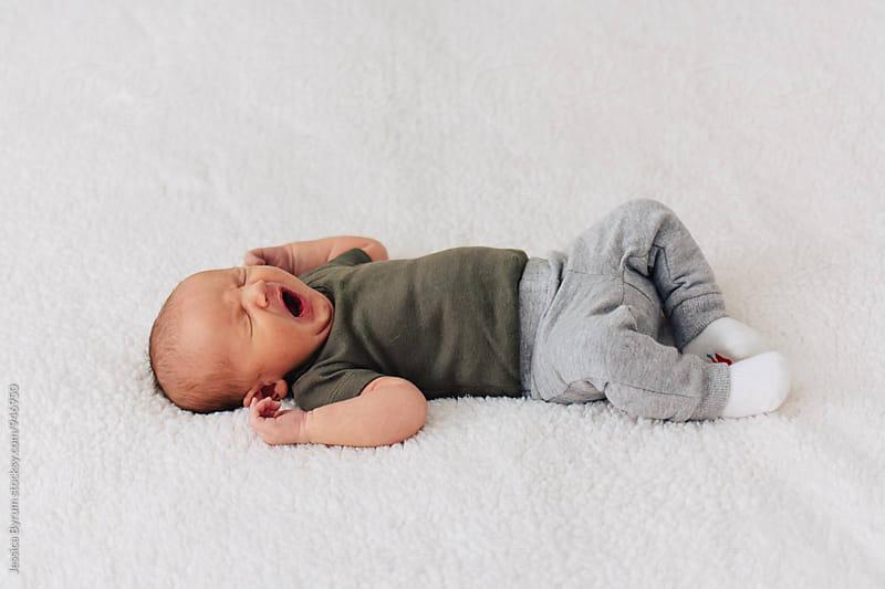 Newborn baby yawning on white blanket by Jessica Byrum for Stocksy United