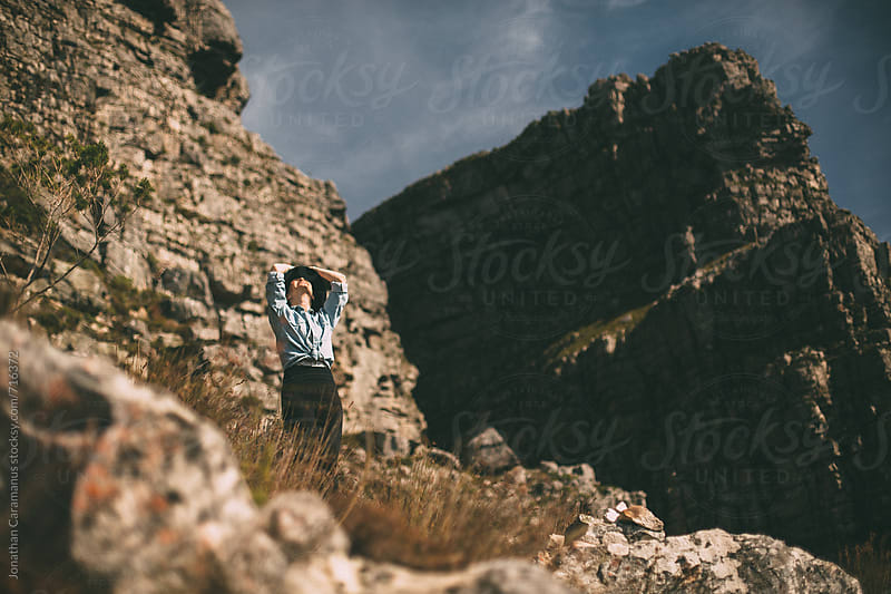 woman standing on rocky mountain surrounded by cliff faces by Jonathan Caramanus for Stocksy United