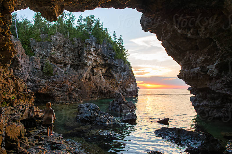 Boy Watching Sunset at the Grotto Sea Cave on Georgian Bay Bruce Peninsula National Park Tobermory by JP Danko for Stocksy United