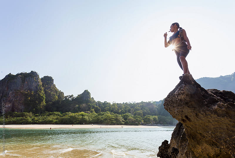 Young asian fitness woman standing on top of a rock overlooking a tropical beach landscape by Soren Egeberg for Stocksy United