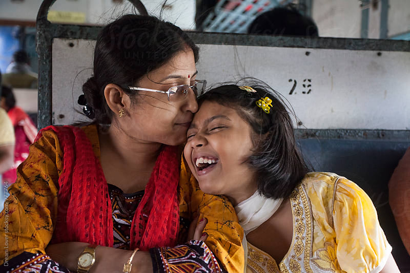Indian woman kisses her daughter in a local train travel by PARTHA PAL for Stocksy United