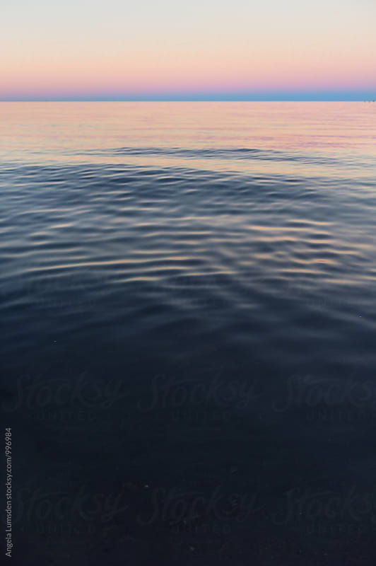 Calm water and sunset colors by Angela Lumsden for Stocksy United