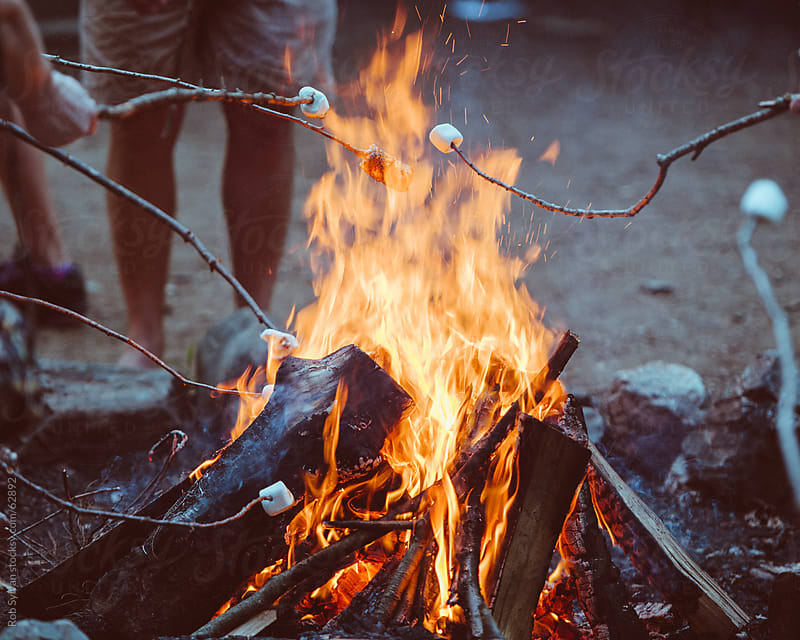 Roasting Marshmallows Over a Camp Fire at Summer Camp by Rob Sylvan for Stocksy United