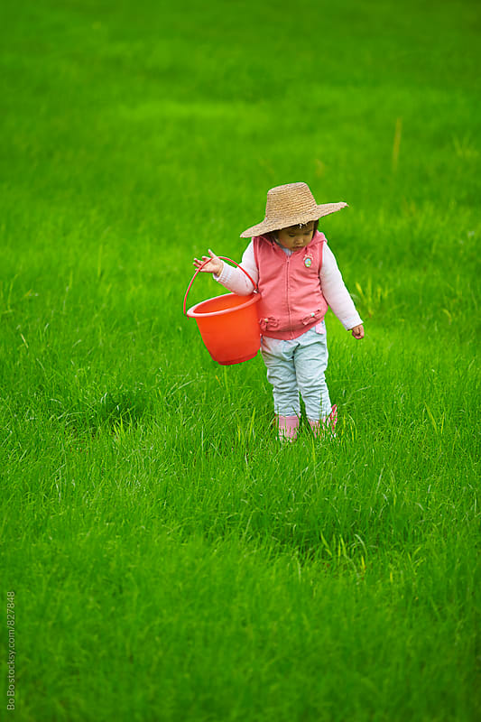 lovely little asian girl walking in the grass land by Bo Bo for Stocksy United