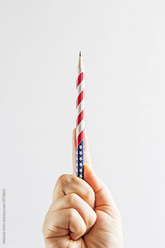 Person holding a stars and stripes themed pencil by Melanie Kintz for Stocksy United