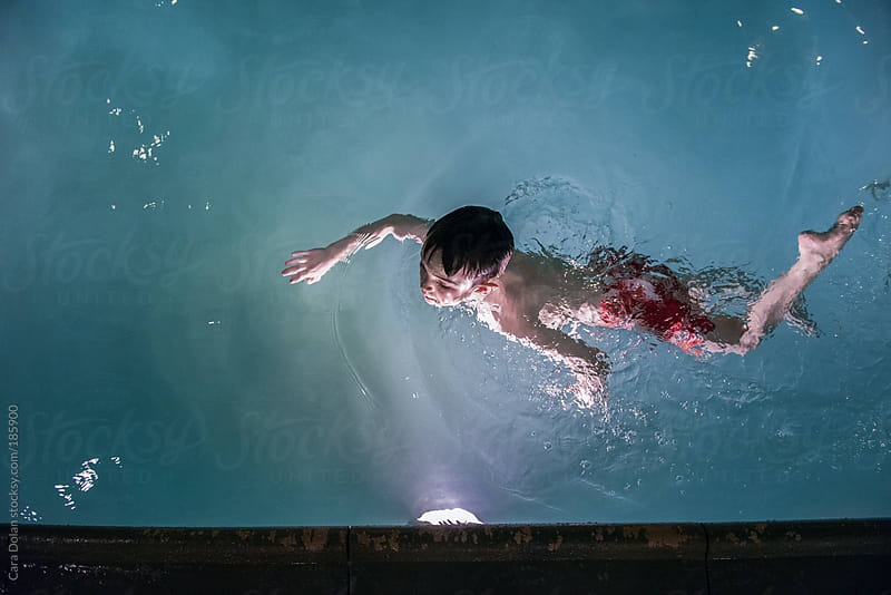 Boy swimming in a pool at night by Cara Dolan for Stocksy United