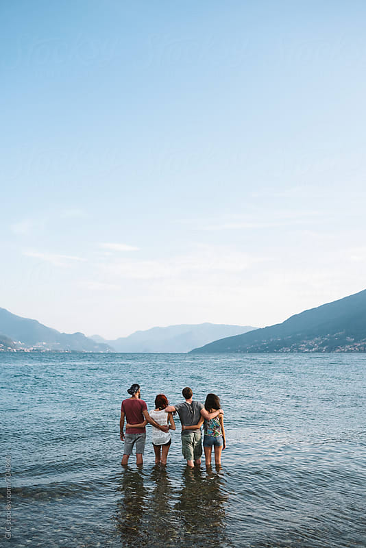 Four friends standing against the lake landscape by Simone Becchetti for Stocksy United