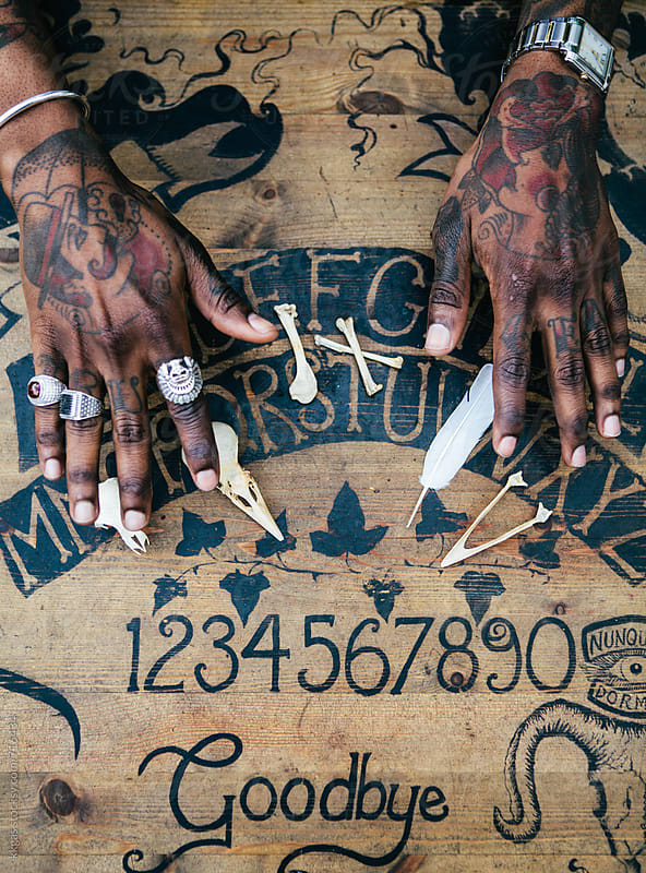 Tattooed hands reading bones on a Ouijaboard by kkgas for Stocksy United