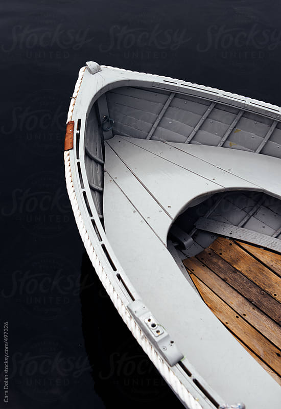 Old wooden boat in dark water by Cara Dolan for Stocksy United