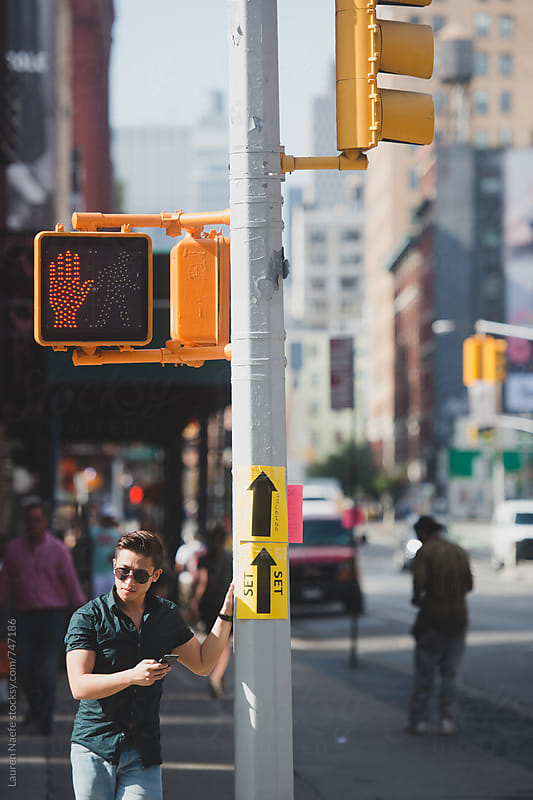 Attractive young man standing in the street in New York City by Lauren Naefe for Stocksy United