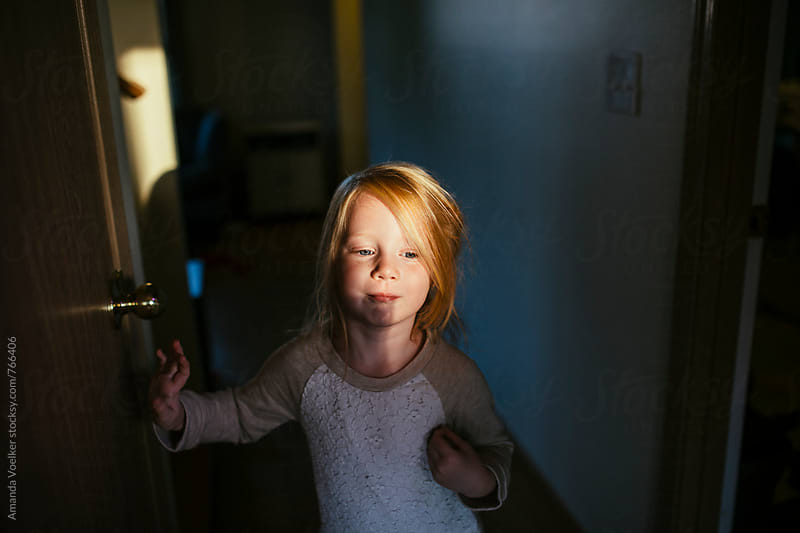 A little girl stands in the bold light and shadow of sunset by Amanda Voelker for Stocksy United