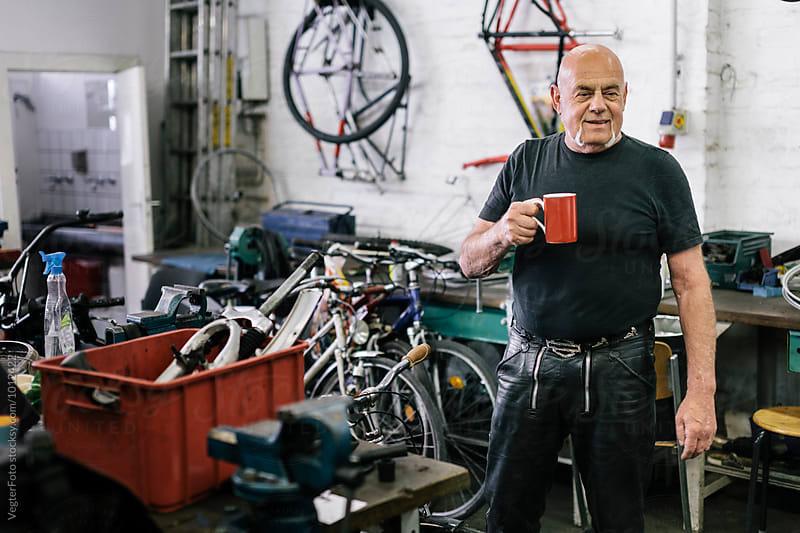 Portrait of Senior adult in Bicycle workshop by VegterFoto for Stocksy United