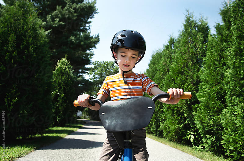 Boy wearing helmet rides a bicycle  by Cara Slifka for Stocksy United