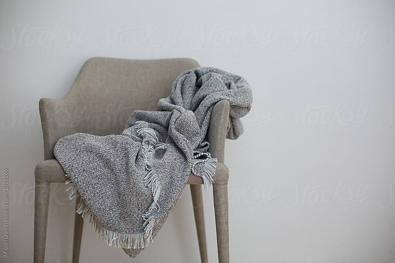 Unfolded grey blanket ona chair by Miquel Llonch for Stocksy United