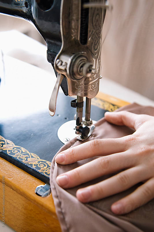 Close-up of woman's hand working with vintage sewing machine by T-REX & Flower for Stocksy United