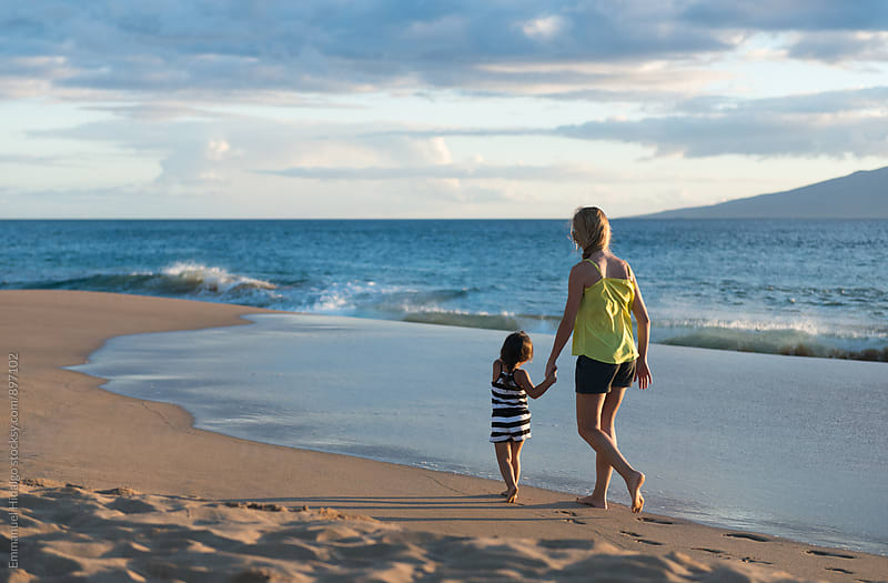 Mother and daughter walking along the shore in Maui by Emmanuel Hidalgo for Stocksy United