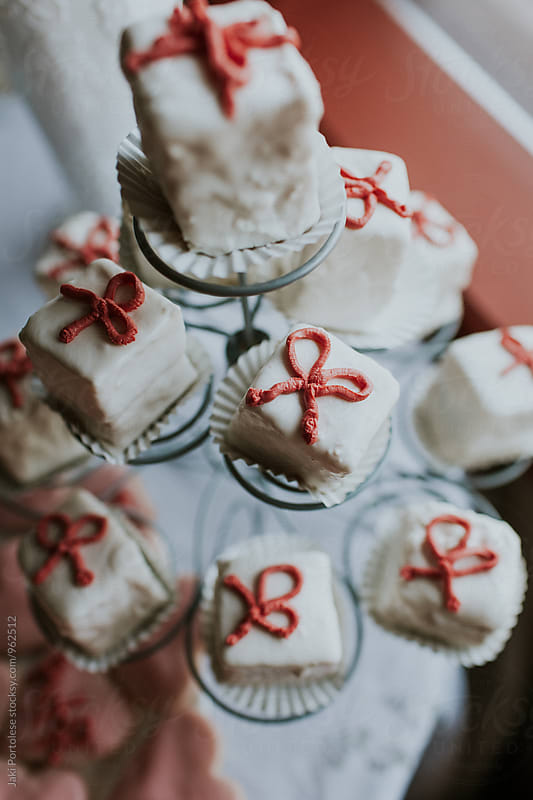 White cakes with pink bows by Jaki Portolese for Stocksy United