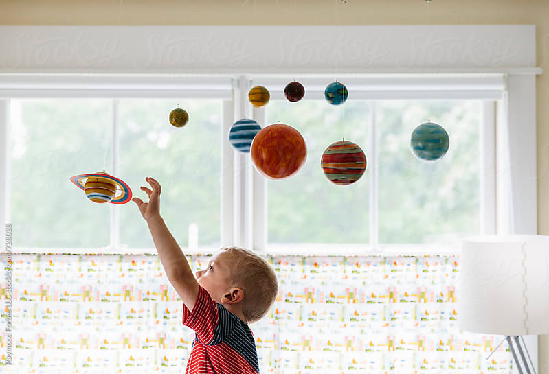 Child Exploring Space and Planet Mobile in Bedroom by Raymond Forbes LLC for Stocksy United