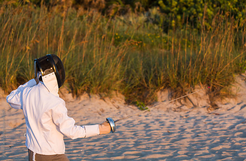 Fencer Practicing on the Beach at Sunrise by Adam Nixon for Stocksy United