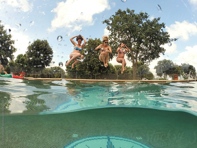 Three friends in bikini jumping in pool by Guille Faingold for Stocksy United