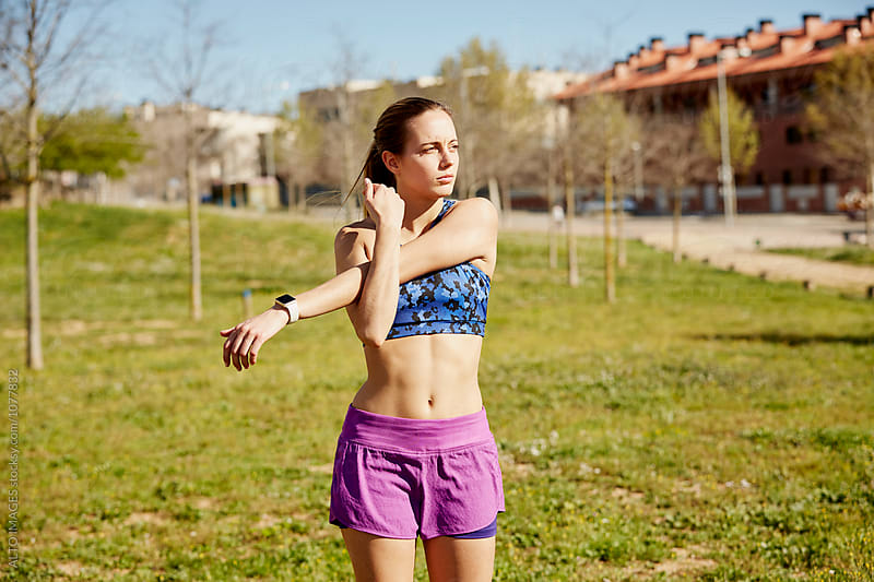 Woman Stretching Before Jogging In Park by ALTO IMAGES for Stocksy United