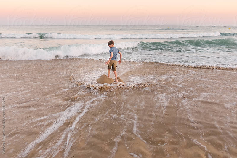Child stands on his sandcastle tower waiting for the waves to crash over it by Rebecca Spencer for Stocksy United