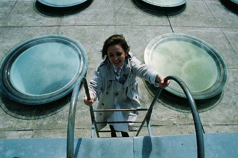 A film photo of young smiling woman lying staying on the stairs by Anna Malgina for Stocksy United