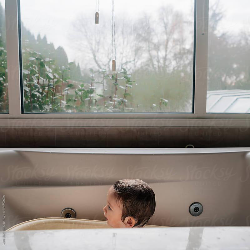 Baby boy taking a bath in a big bathtub by Ivan Bastien for Stocksy United