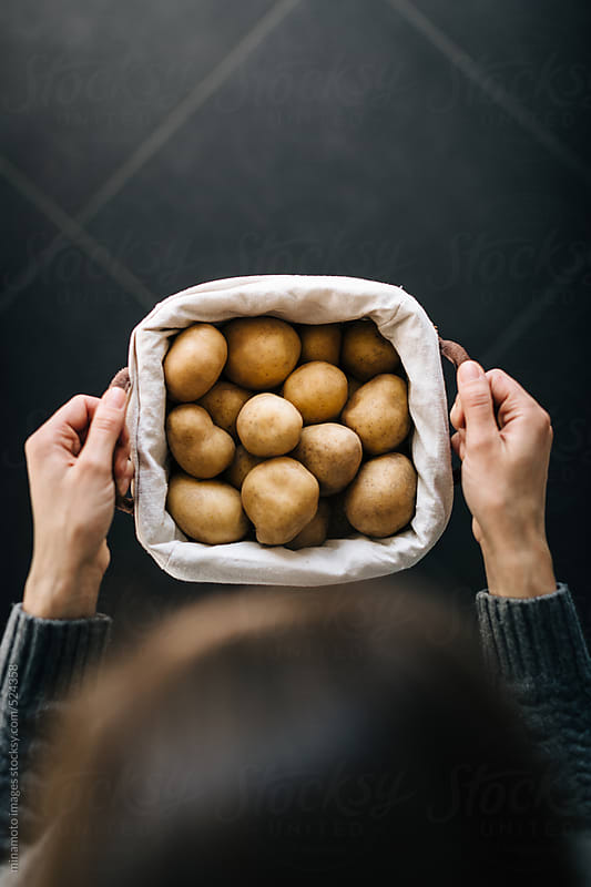 Woman Holding Basket With Fresh Potatos by minamoto images for Stocksy United