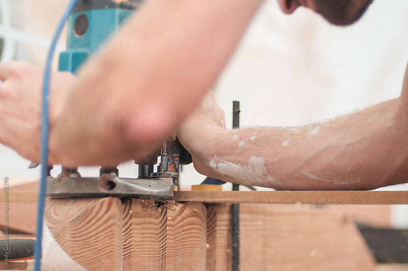 A carpenter works on some wood with a power tool by Andy Campbell for Stocksy United